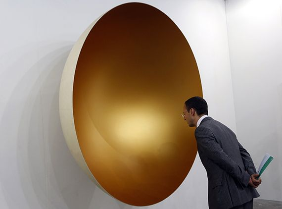 A visitor looks at an artwork by Indian sculptor Anish Kapoor at Art Basel's 2015 edition in Hong Kong