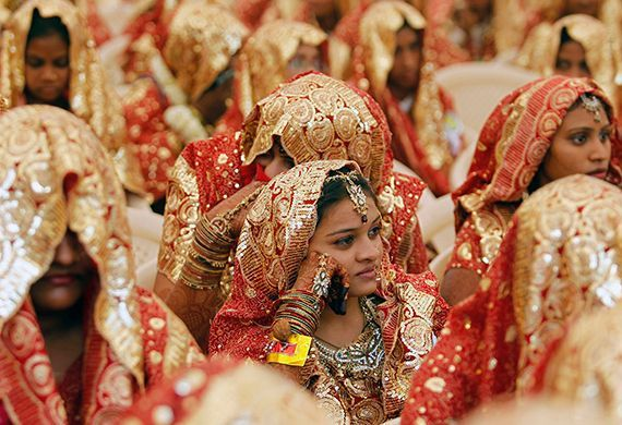 Muslim brides sit as they wait for their weddings to start during a mass marriage ceremony in the western Indian city of Ahmedabad